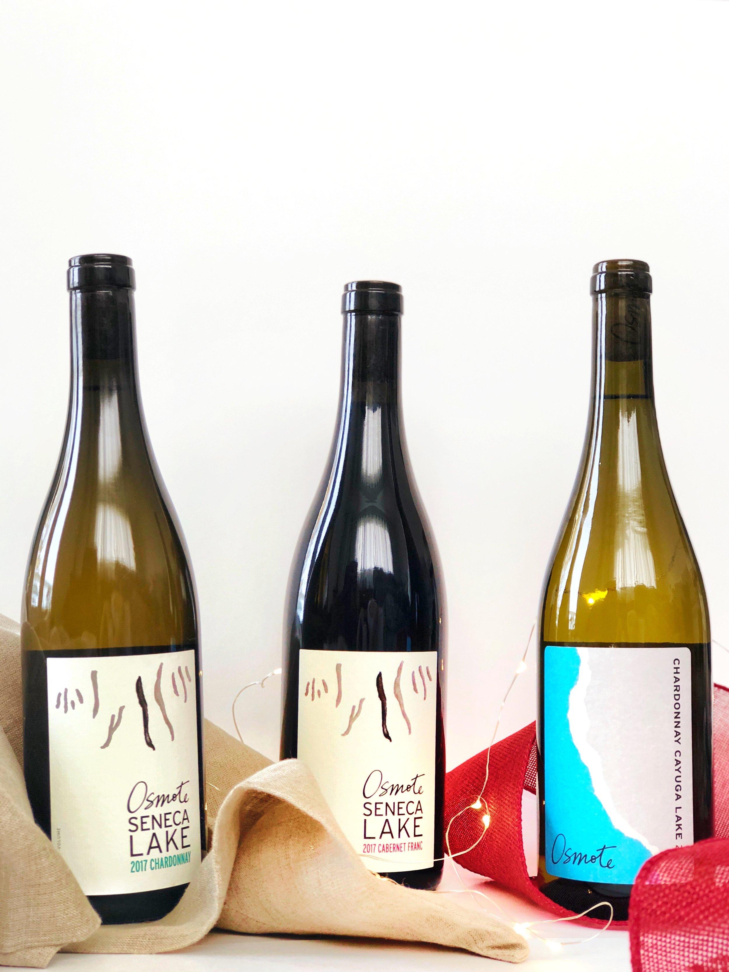 3 Osmote wine bottles on burlap backgrounded by white