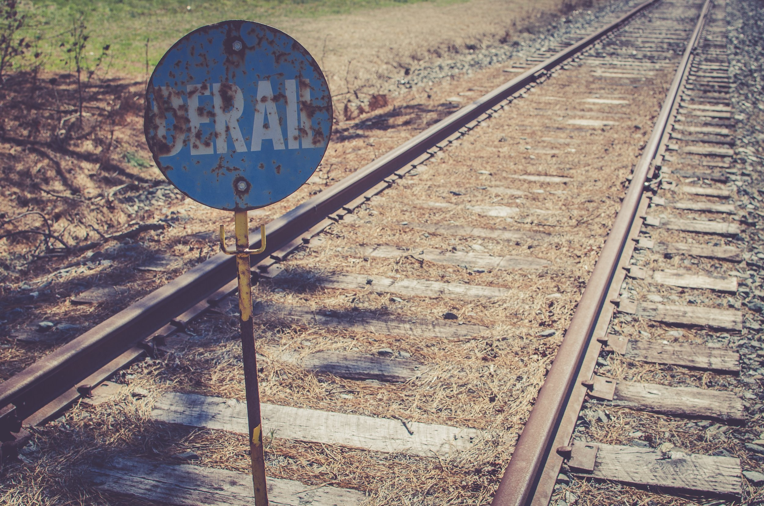 rusted derail sign by abandoned tracks.jpg