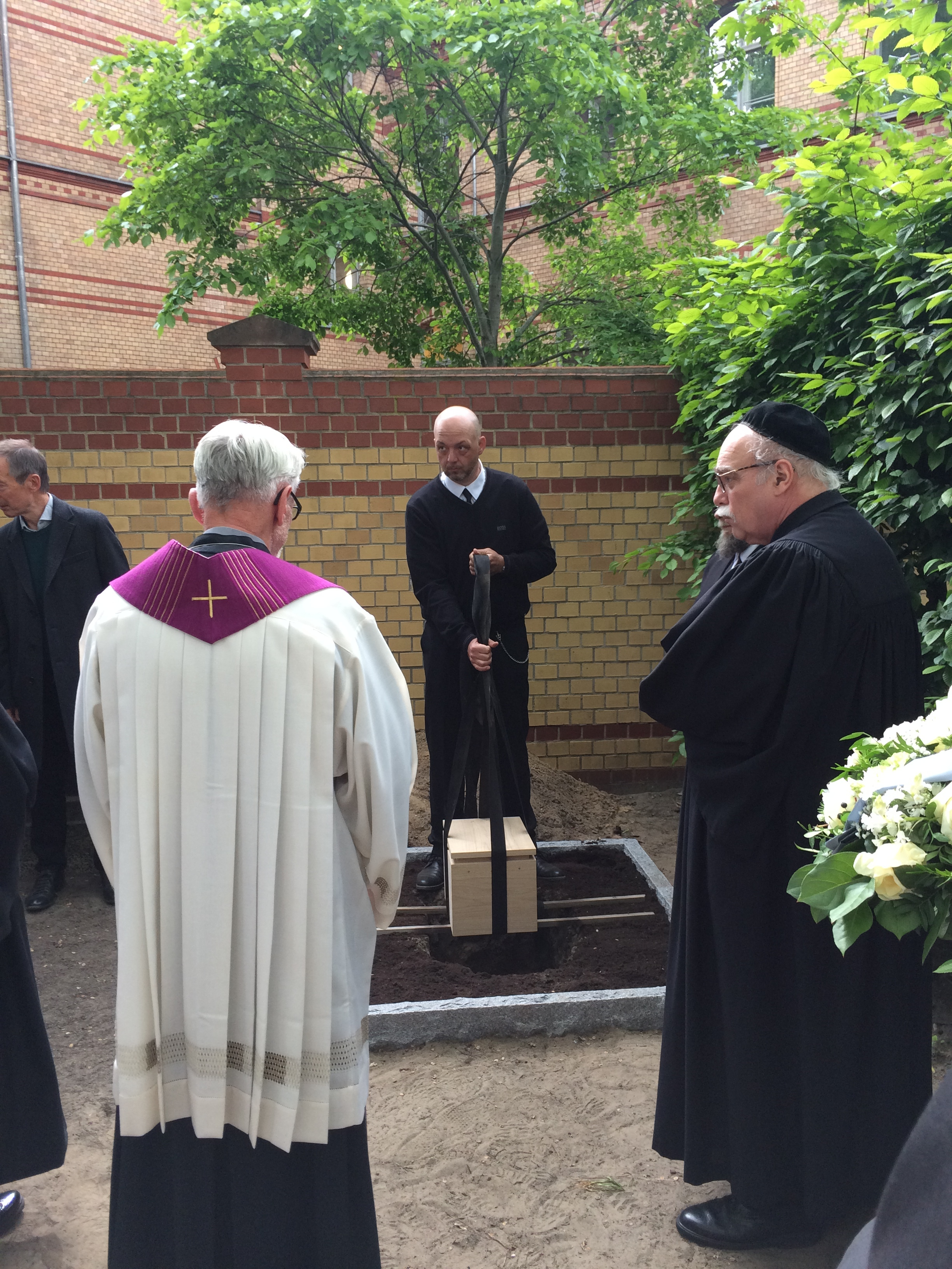 Dr. Johannes Tuchel, the historian who heads the German Resistance Memorial, lowers the remains as part of the burial ceremony.  Photo by Art Heitzer