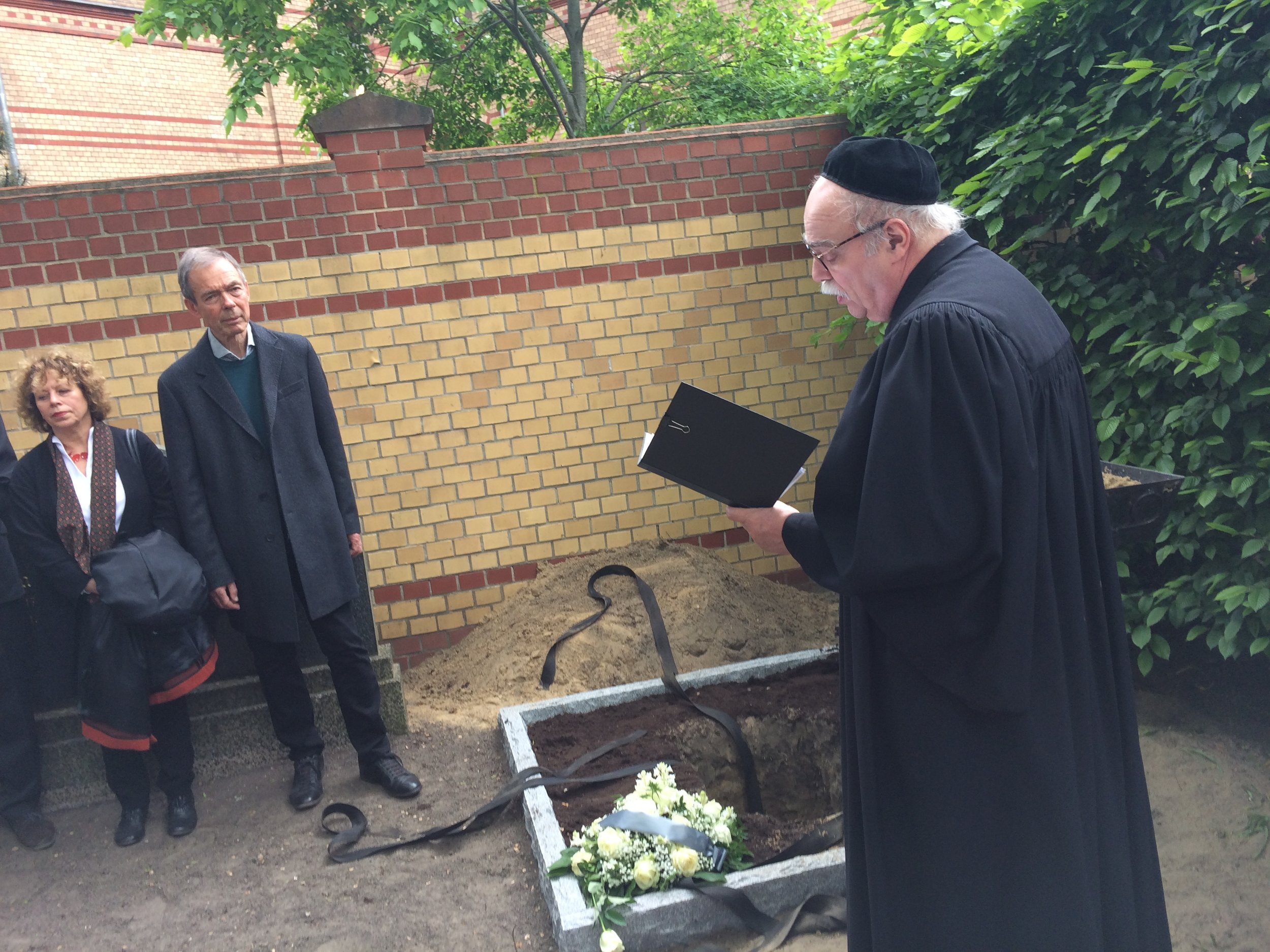 "A Rabbi reads from the Torah (right) as Hans and Helle Coppi (left) observe the burial ceremony. Hans is a researcher and historian on the German resistance, and both of his parents were executed for being part of the ""Red Orchestra""  Photo by Art Heitzer"