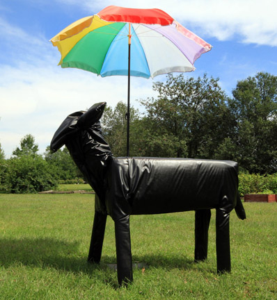 """Eva Whorley/Bovine Divan   Repurposed/recycled wood, metal, batting,pleather, and salvaged umbrella  7"""" x 3' x 4'  Bovine Divan was created with the intent of having people interact with it. It is designed to be easily moved and sat upon to view the other art works on the farm. The umbrella is to add to the comfort of the sculpture and viewer. Bovine Divan was made of reclaimed and reused materials and designed to blend in with the herd as so many of us do."""