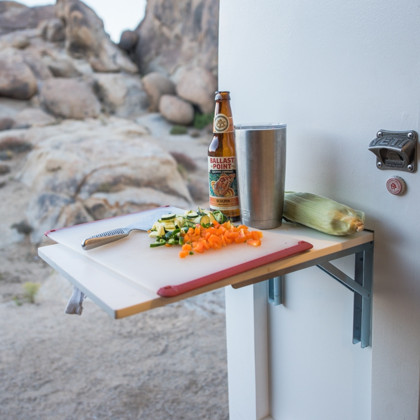 Fold Up Table - This table can be installed on different locations throughout your van to give you a convenient location to place a beverage, or a hot plate of food. It can carry over 20 lbs so it also works great when installed on the side of a galley to create additional counter space when cooking.