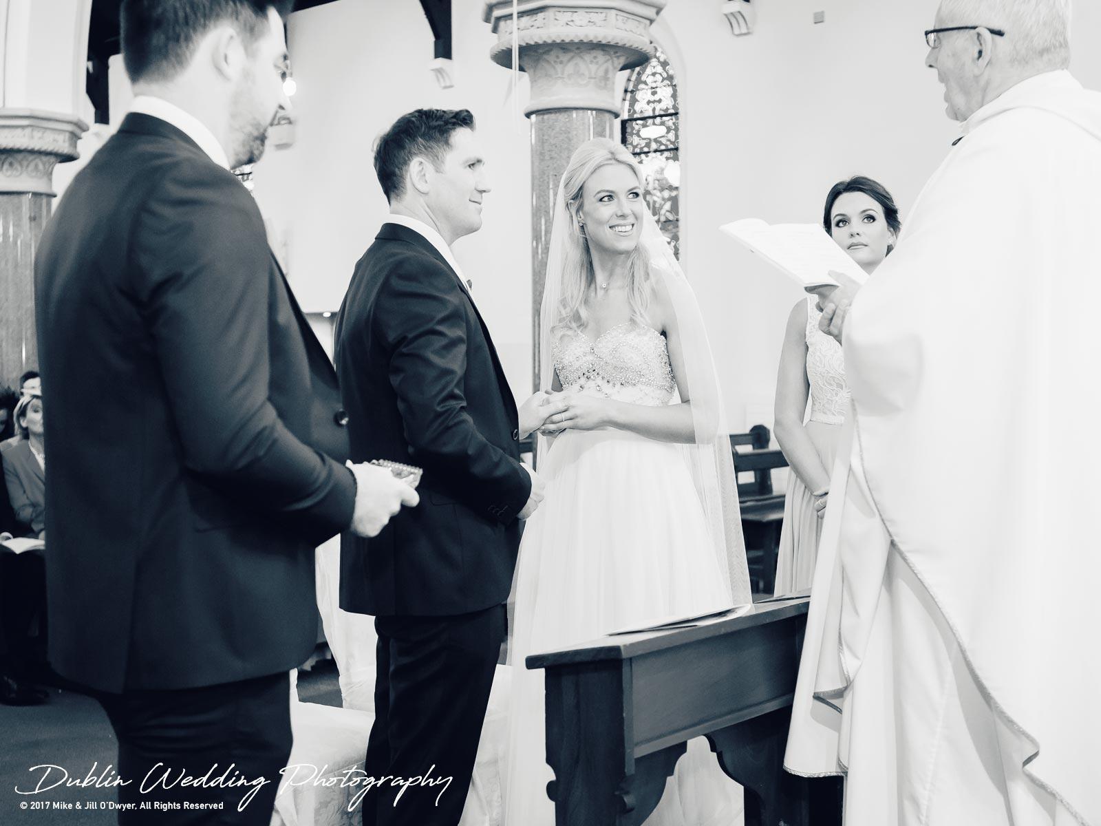 K Club, Kildare, Wedding Photographer, Dublin, Bride and Groom smiling at priest