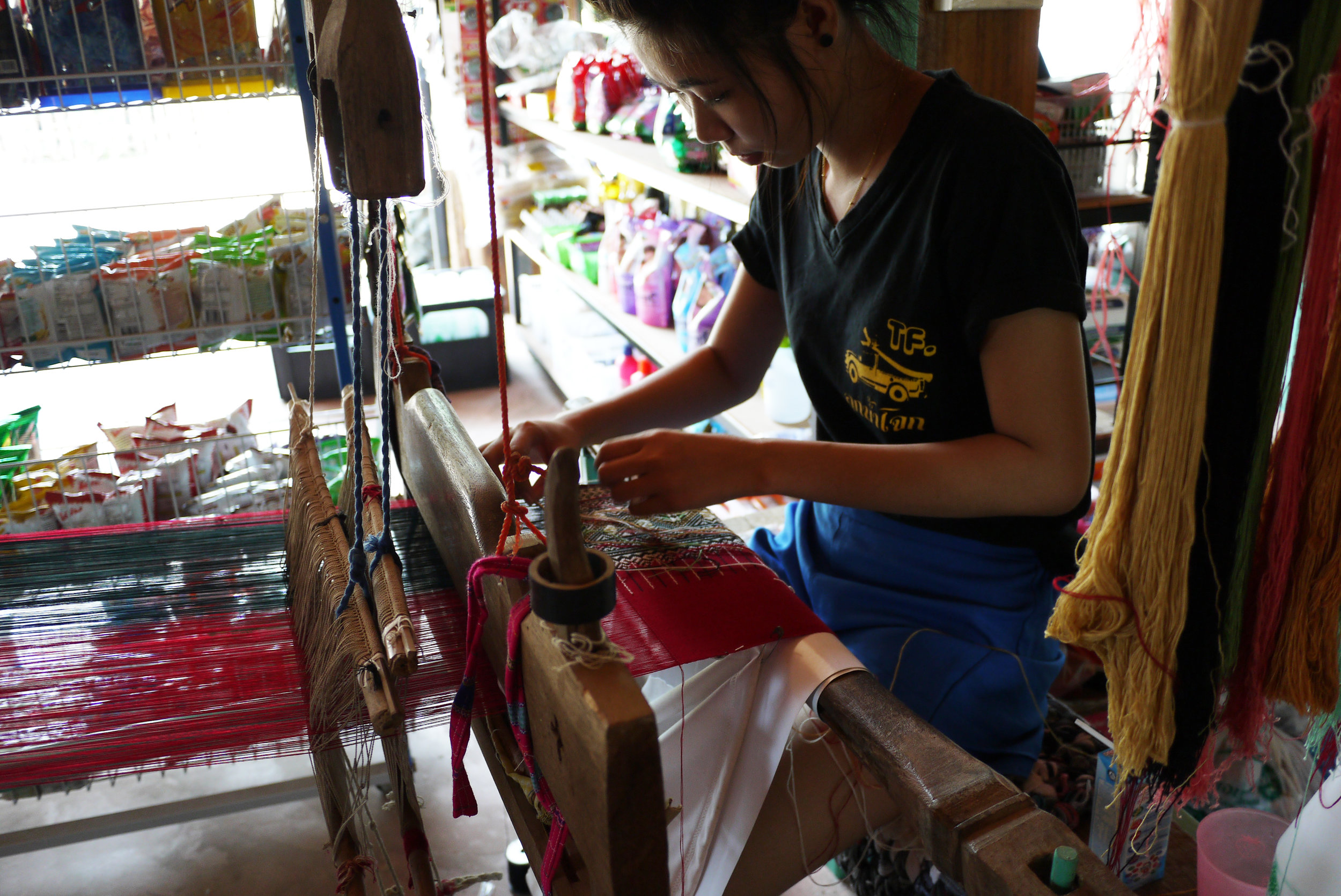 A young weaver working at the back of a convenience store in Mae Chaem