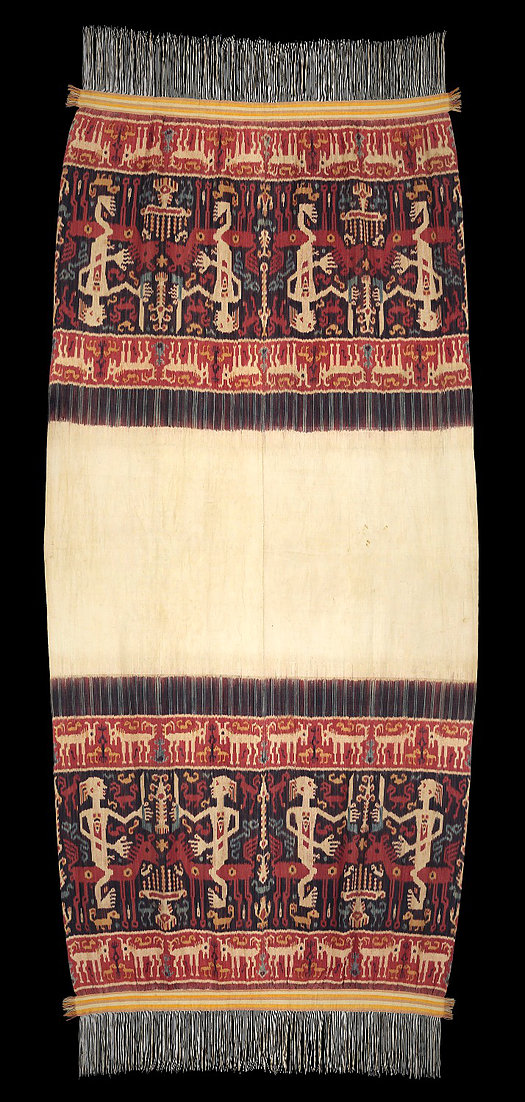 C. 1900,  Hinggi Kombu, ceremonial shoulder cloth for royalty.  Made with handspun cotton warp faced Ikat featuring large male figures and animals on the sides of large empty white center.  All natural dyes. Sumbanese, east Sumba, probably Kenatang, Indonesia.   118 X 244 cm   Samyama  Collection.