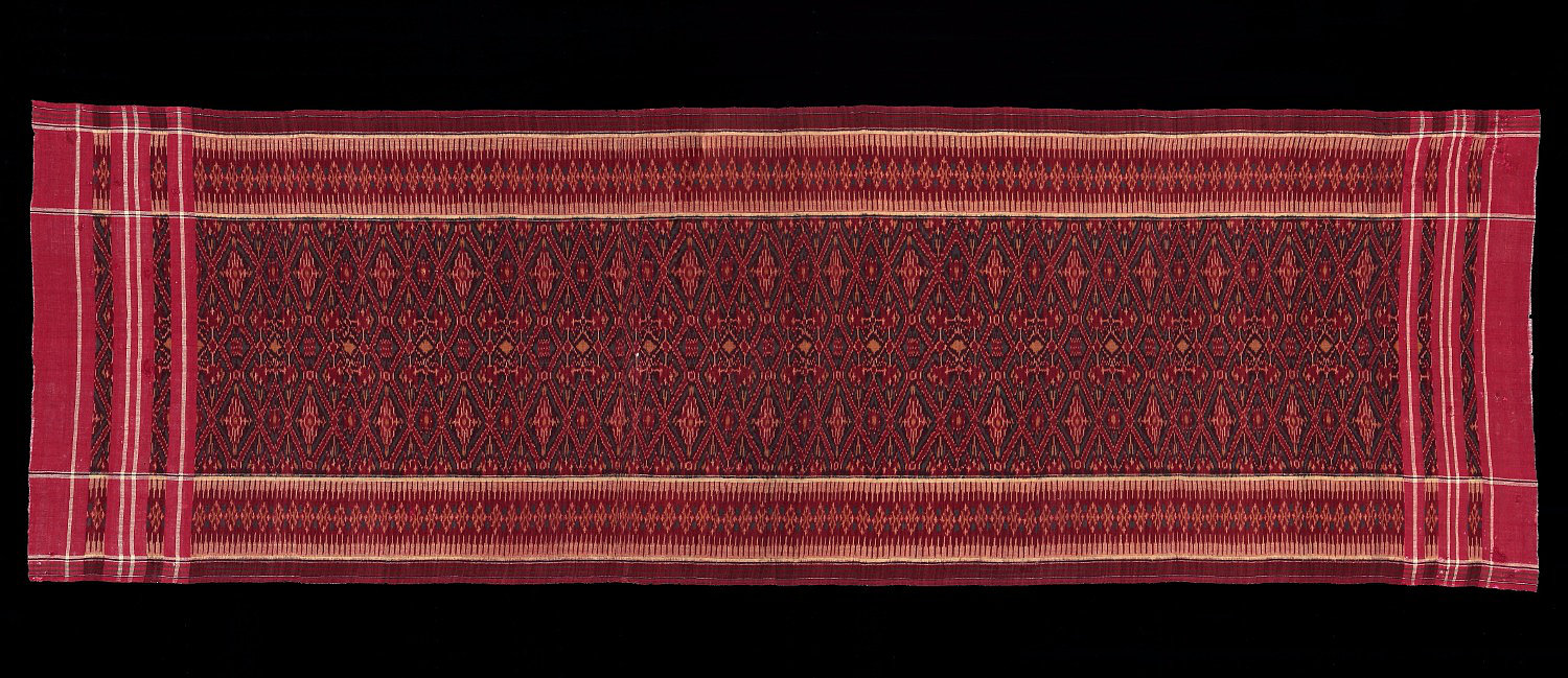1940-60s Cepuk, sacred ceremonial cloth.  Made of red cotton weft ikat copying Indian patola design and layout. Bali people, Nusa Peninda, South Bali, Indonesia.  240 x 77 cm   Samyama  Collection.