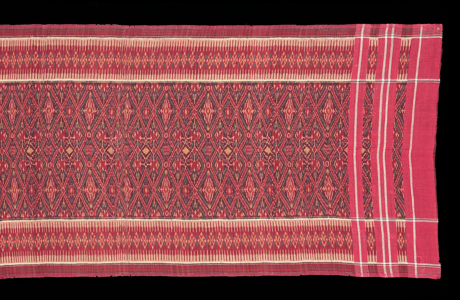 Detail of 1940-60s Cepuk, sacred ceremonial cloth.  Made of red cotton weft ikat copying Indian patola design and layout. Bali people, Nusa Peninda, South Bali, Indonesia.  240 x 77 cm   Samyama  Collection.