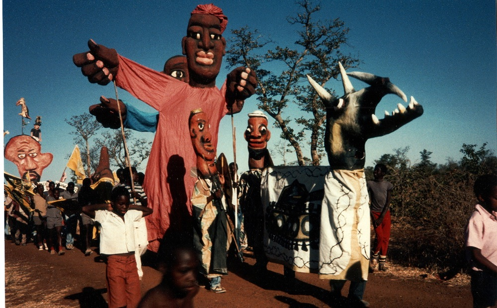 Crying africa - Refugees escaping Angola and Namibia lead parade with anti-apartheid horned beast, Dukwei Refugee Camp, Botswana, Africa 1987