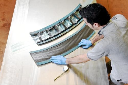 Technician working on carbon fiber for automotive application.