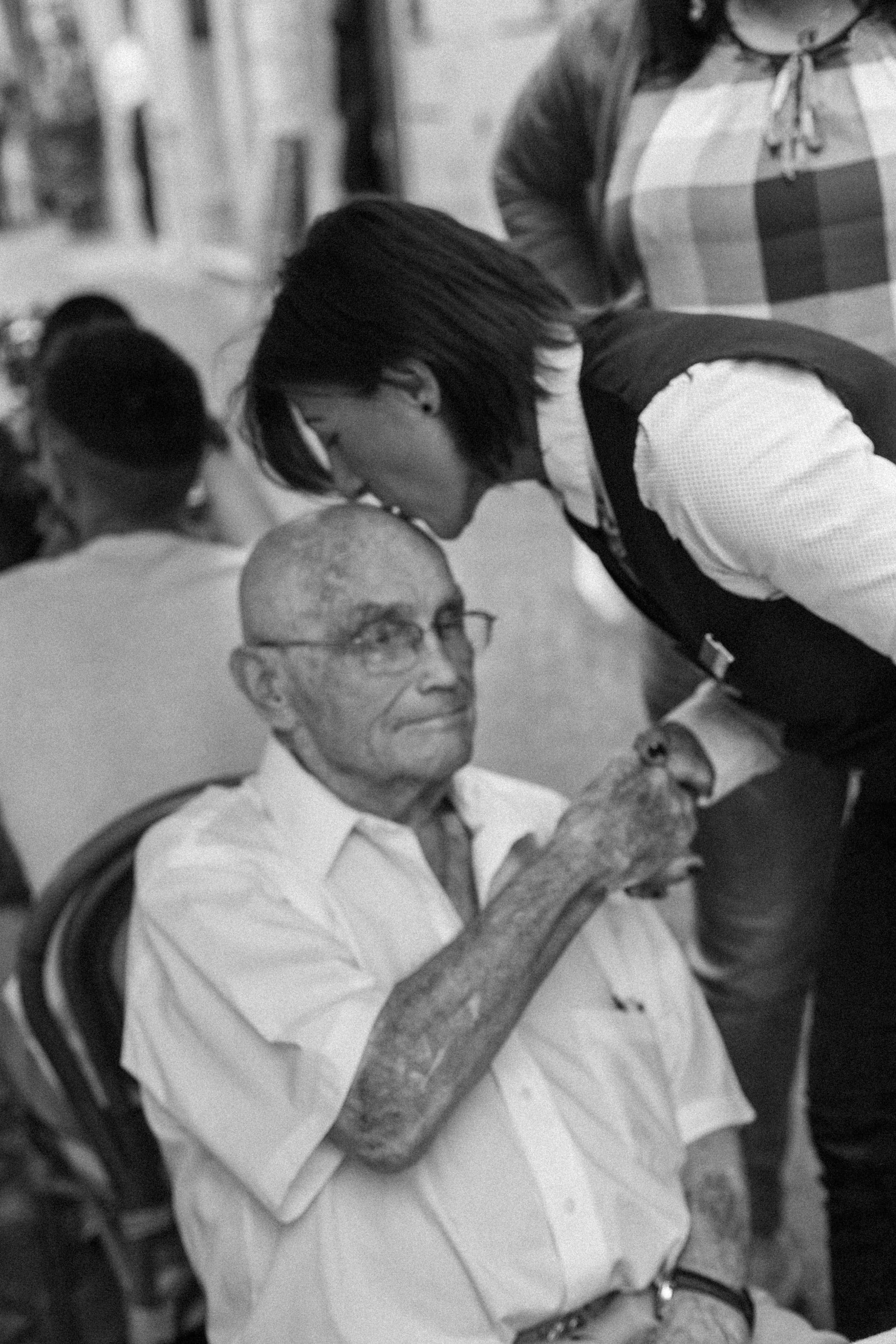 A waitress gives a 100 year old man a kiss on his head for his birthday