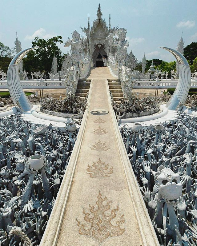 "Wat Rong Khun, The White Temple In Chang Rai. Chalermchai Kositpipat, is the Thai visual artist who designed and renovated the White Temple. The temple was opened to the public in 1997. It is 15km south of Chang Rai city.  You can combine a trip to the White Temple with a visit to the Blue Temple or the Baandam Museum or Black House.  Our favorite hotel is @lemeridienchangrai It's a quiet hotel with beautiful grounds.  The photograph features the bridge of ""the cycle of rebirth"". In front of the bridge are hundreds of outreaching hands that symbolize unrestrained desire. The bridge symbolizes that the way to happiness is to forgo temptation, greed and desire.  Follow us @optionescape for more travel tips.  Please feel free to ask us any questions about our experiences abroad. We were not sponsored for this trip. We paid our own way and our recommendations and opinions here are our own.  #thailandtravel #amazingthailand #whitetemplechiangrai"