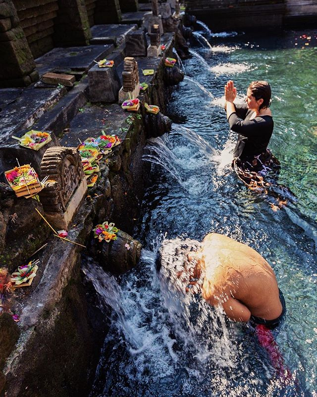 Tirta Empul Temple, Manukaya Village, Bali. The temple was completed in 962, during the reign of Chandra Bhayasingha, the fourth king of the Warmadewa Dynasty.⁣ ⁣ The holy spring water here pours out through 30 waterspouts into two sacred bathing areas called petirtaan. They are used for a purification ritual known as 'melukat'. Behind the purification pools is large a courtyard with a sacred spring which feeds the pools. ⁣ ⁣ The temple is close to the beautiful and ancient site of Gunung Kawi (11th century temple and funerary complex) which we also recommend visiting if you are staying in the area around Ubud. ⁣ ⁣ Another site built in the 9th century which is also worth a visit is the temple of Goa Gajah (The Elephant Cave). ⁣ ⁣ Please follow us @optionescape for more travel tips. ⁣⁣ ⁣⁣ Please feel free to ask us any questions about our experiences abroad. We were not sponsored for this trip. We paid our own way and our recommendations and opinions here are our own.⁣