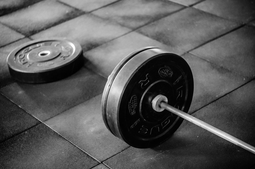 Barbell with extra weight sitting next to it on the floor