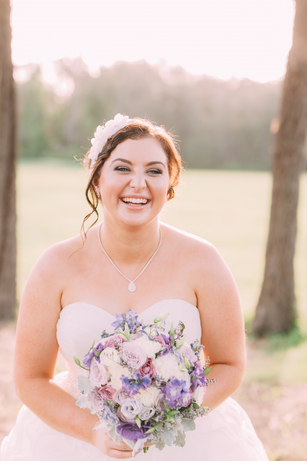 Bride smiling holding bouquet of flowers