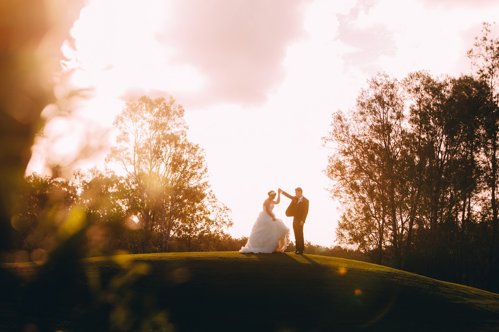 Bride and groom dancing on grass hill at sunset