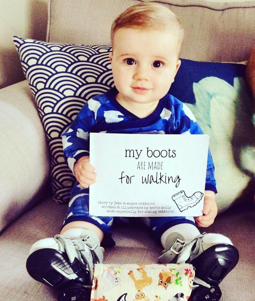 "Marie was commissioned to write a book for little Oakley. Oakley was born with a club foot and needs to wear corrective boots for most of his formative years. ""My Boots Are Made For Walking"" is about accepting the differences we are born with, which make us special. This photo was sent from Oakley's parents, they read the book together every night. As you can see, Oakley loves his book. - Pictured: young Oakley with a book commissioned and written just for him!"