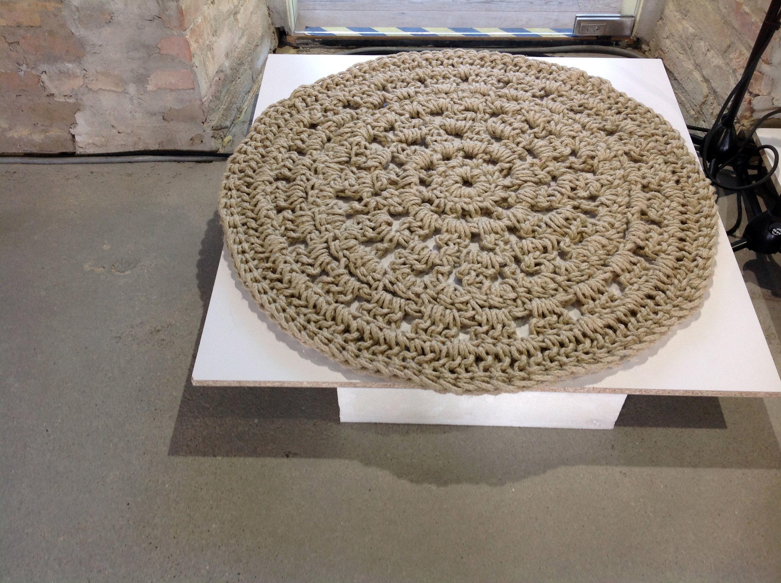 KÖRÖS KÖRÜL  - Tervező: Lőrincz Lili HannaTermékismertető:Természetes alapanyagból, horgolással készült kül- vagy beltéri szőnyeg. A hagyományos horgolás újragondolásával a vastag merev, szálak is felhasználhatóak, melyek izgalmas struktúrafelületet képeznek, ami kiválóan alkalmas szőnyeg készítésére is.