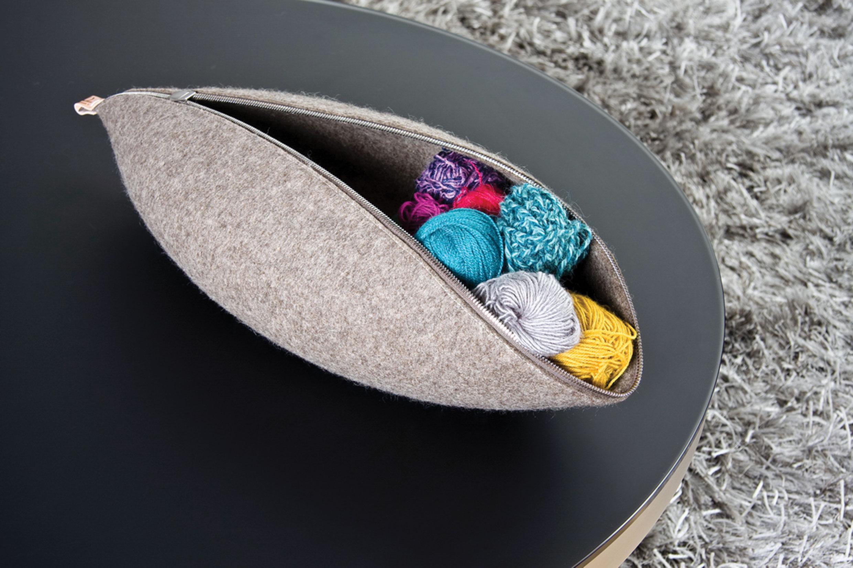 klocc tároló család - Tervező: Ducsai JuditGyártó: Ducsai.Leather.GoodsTechnika: KloccolásMéret: kb. 70 x 40 cmAnyaghasználat: 1 cm vastagságú 100% szürke designfilc, növényi cserzésű natúr bőrA kalapos mesterségből átemelt technológiával a gyapjú vizese állapotában való könnyű formázhatóságát használja ki. A kloccolt technológián alapuló tárolókollekciót letisztult, organikus vonalvezetés jellemzi. Szabás nélküli formaképzésre és merevítés nélküli formatartásra fókuszál, amit a filc sokoldalú tulajdonsága tesz lehetővé. Az egyetlen darabból kialakított tárolók formáját az összeillesztés módja, például a zipzár végpontja határozza meg, illetve eltolásával a tárgy más alakzatot vesz fel.