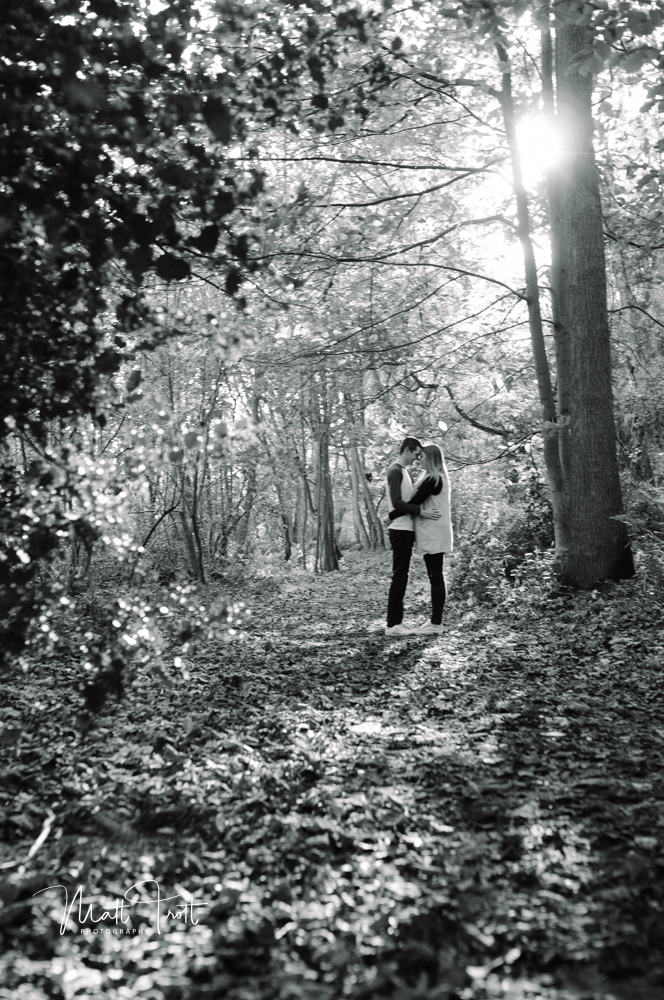 Couple cuddling on engagement shoot in Ashenbank wood