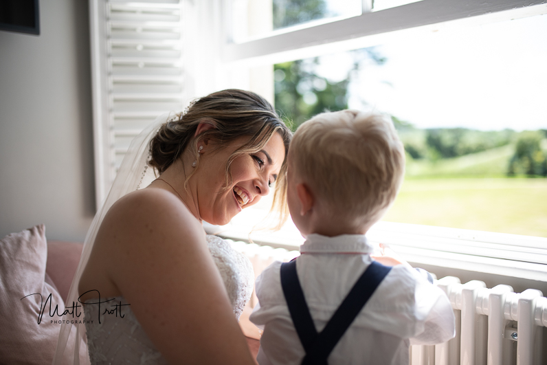 Bride laughing with son out of the window at northbrook park