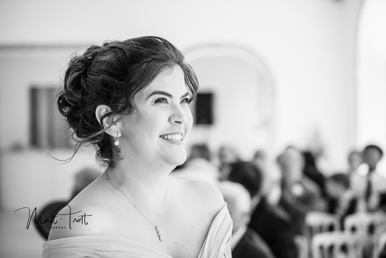 Bridesmaids smiling as she walks down the aisele at northbrook park