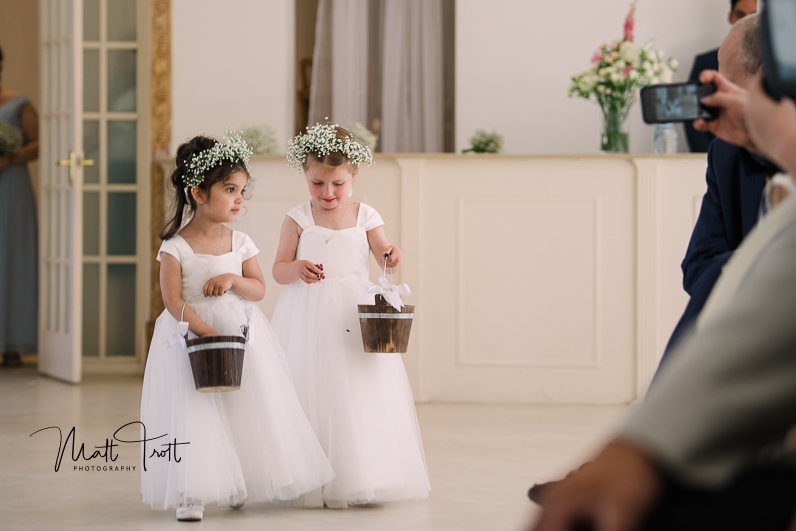 Flower girls dropping petals in the aisle at Northbrook park