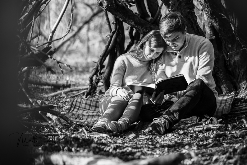 Couple reading book on engagement shoot in kent under a tree