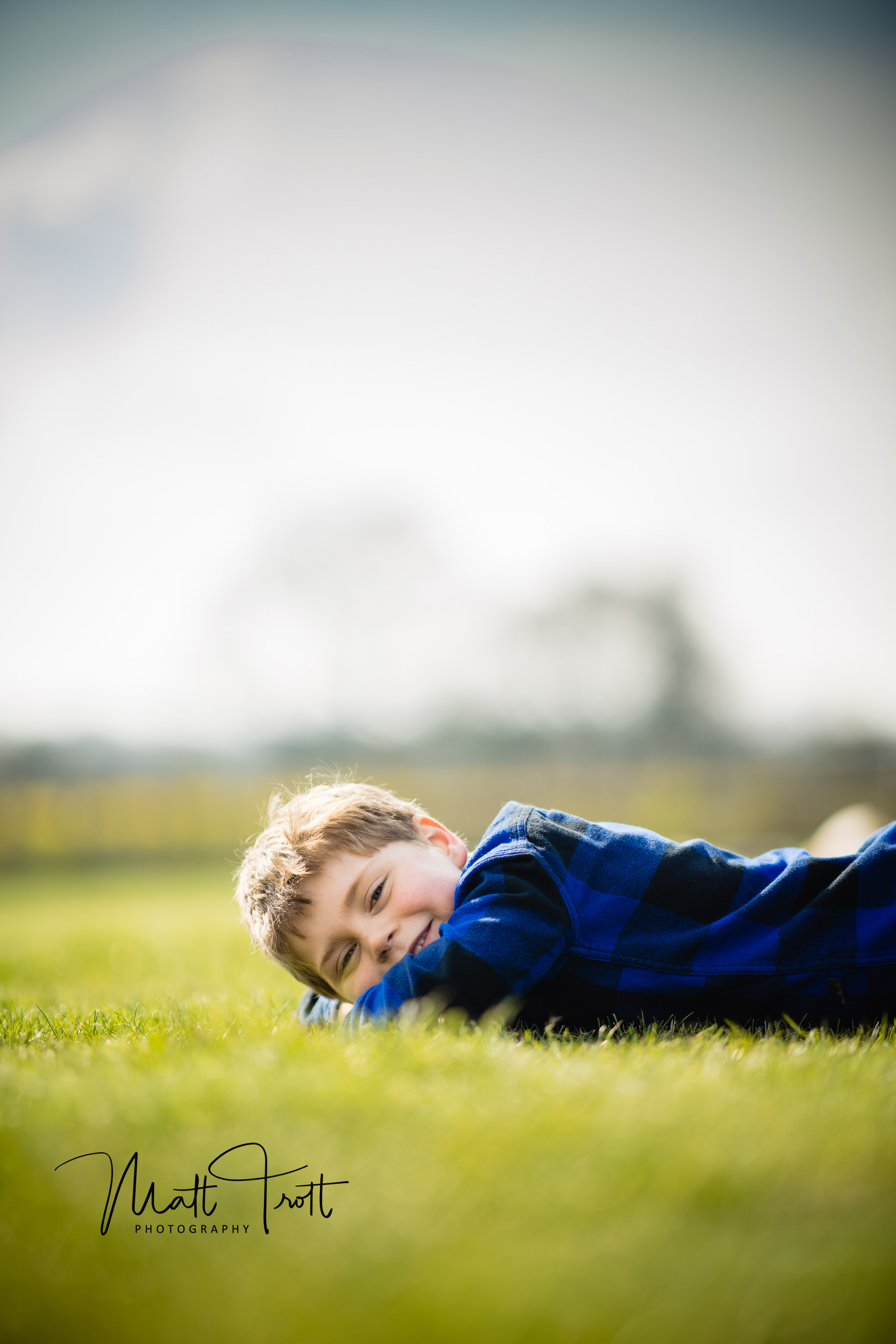 Boy laying on grass smiling.JPG