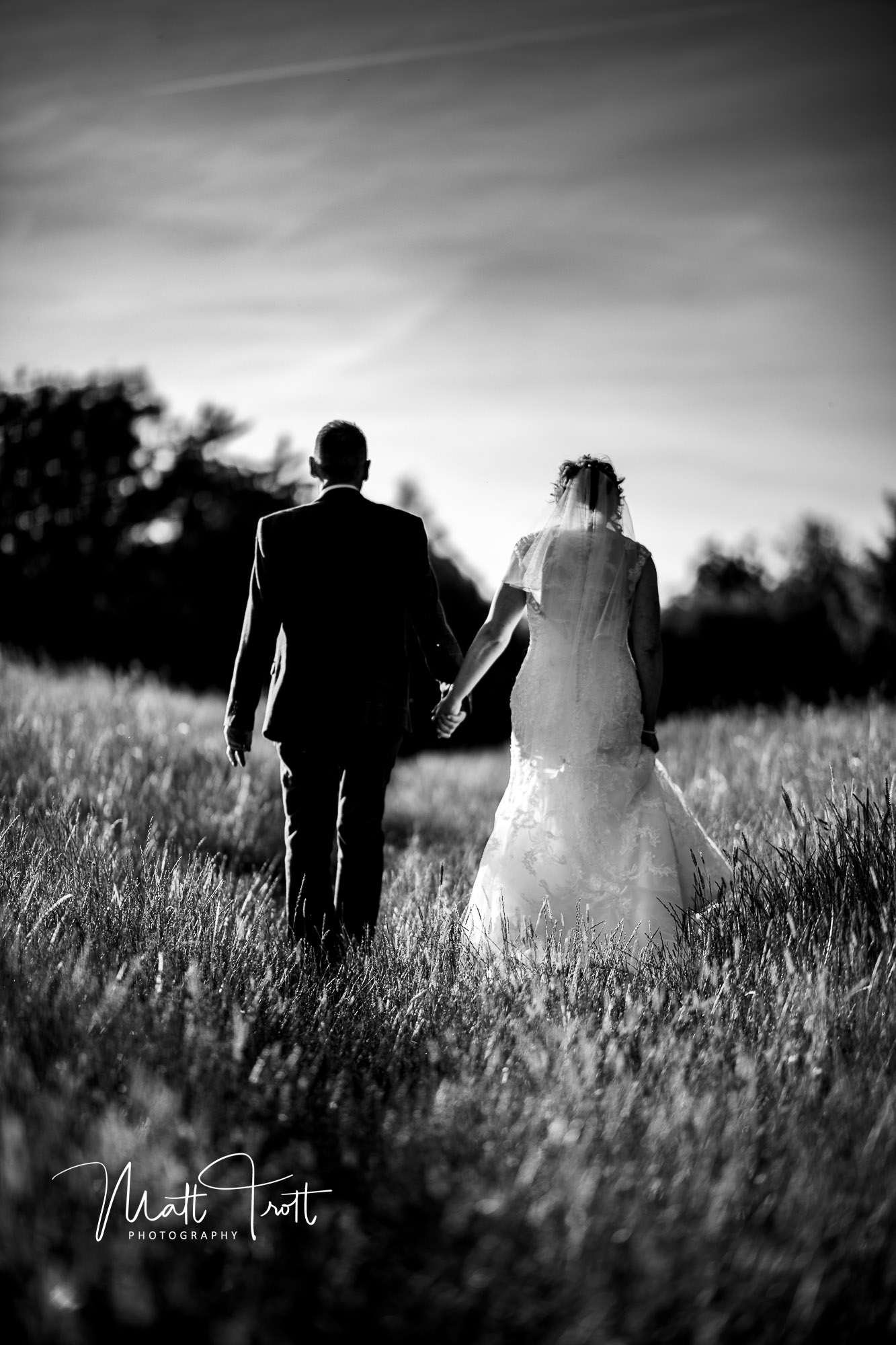 Bride and groom walking through long grass at crown lodge kent