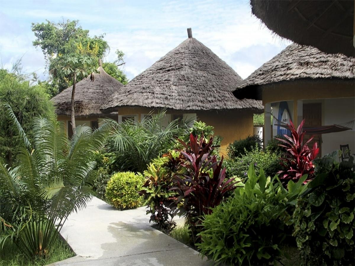 - El complejo, formado por bungalows, compartidos para 2 ó 3 personas, con baño privado, wifi, terraza y ventilador,estárodeado de jardines, una zona de material de surf donde guardar los equipos, oficina de información, bar y restaurante.Se encuentra a escasos 10 minitos de la playa, en la entrada del pueblo de Kabrousse, en cuyas inmediaciones encontrarás bares, tiendas, farmacia, y otros negocios locales.
