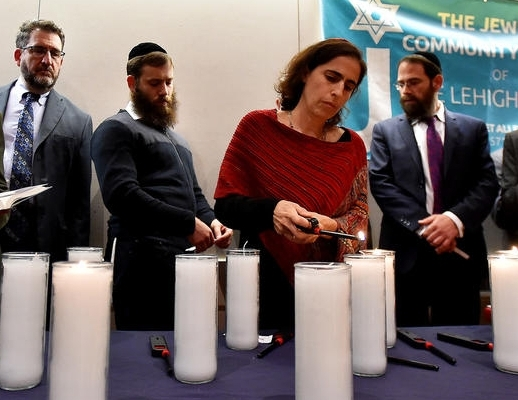 Lighting a memorial candle at Lehigh Valley Interfaith Vigil, October 31, 2018. At the vigil, attended by about 1000 people, were clergy colleagues of many different faiths, showing their support for our community.