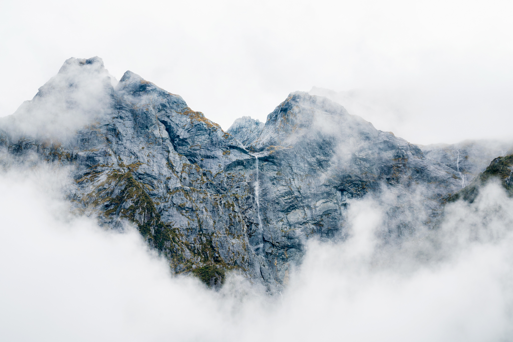 An opportune break in the fog reveals a lone waterfall tumbling down a steep rock face in Milford Sound. (Talman Madsen)