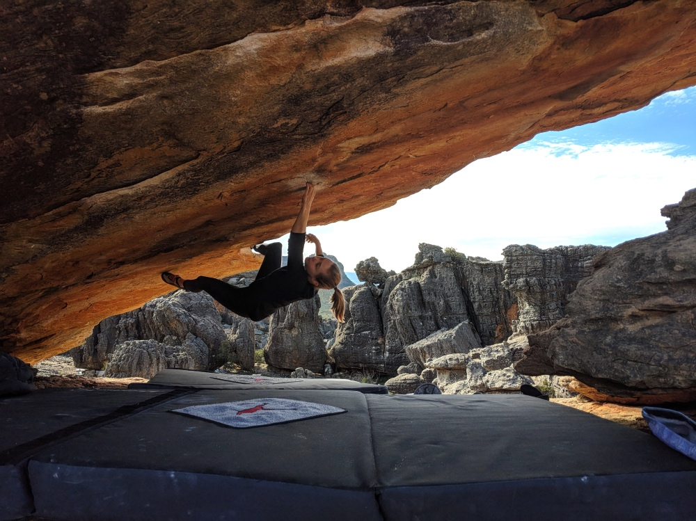 Amy in her preferred environment, upside down, on Roof is On Fire (V6), Rocklands, South Africa.  Gordon Fowler