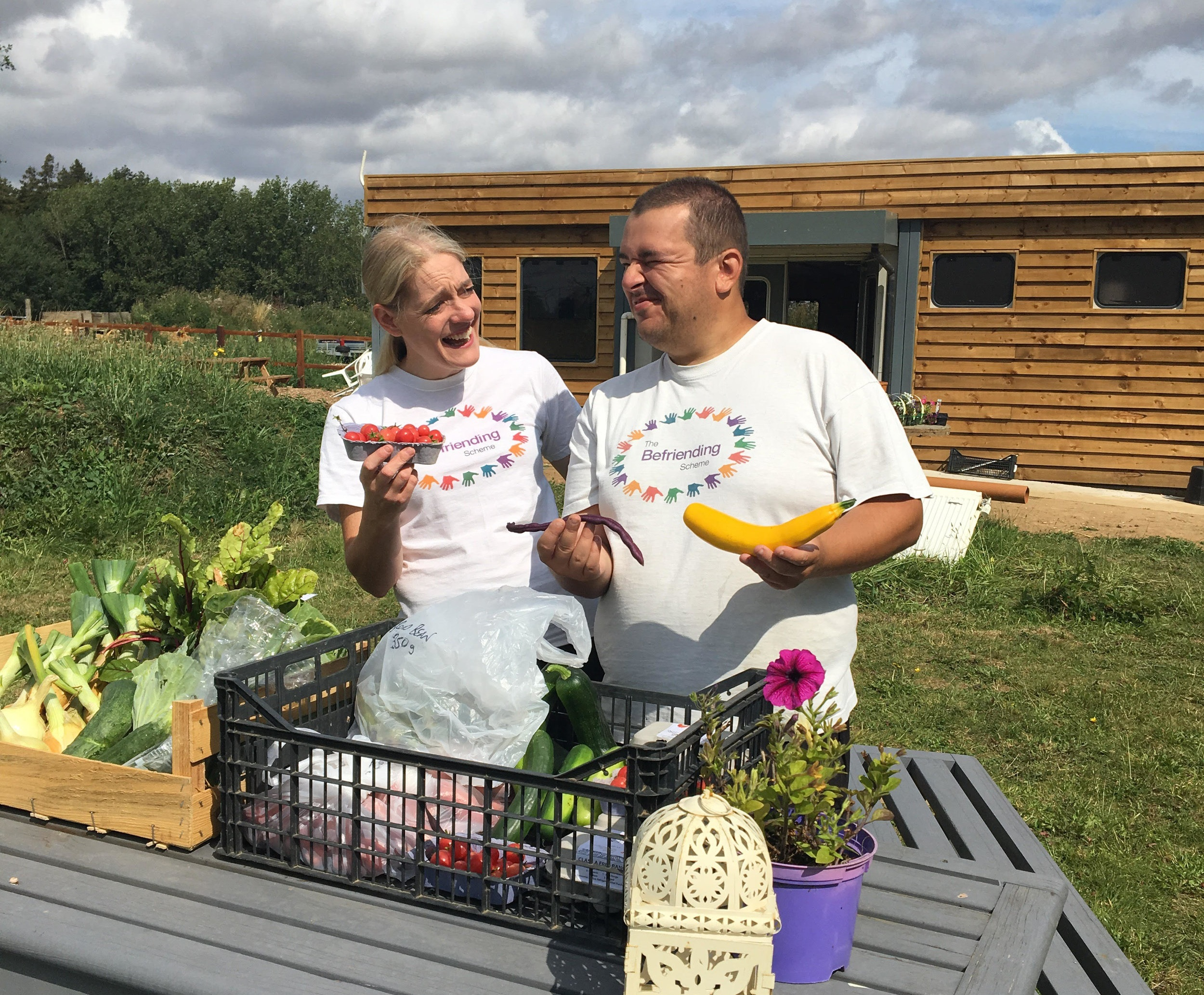 Community Farm Leader, Ashley displaying the fruit and veg harvested from the farm with long-term-volunteer, Vincent.