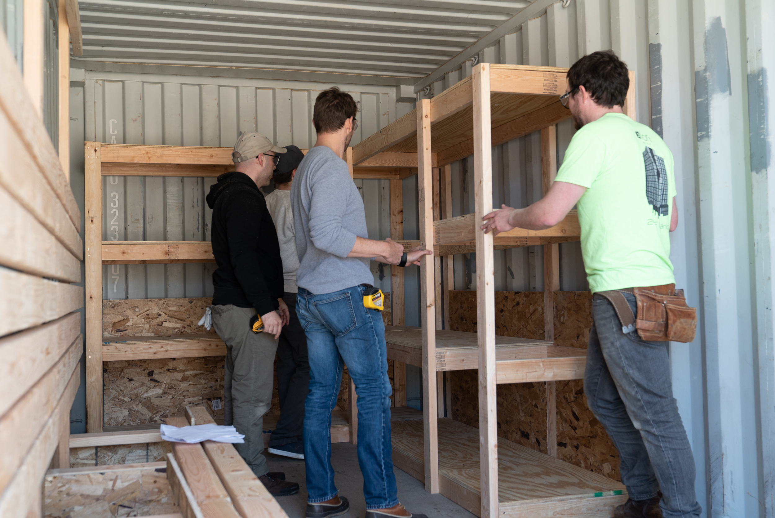 Rafael, Andrew, Micahel and Stephen install shelving.
