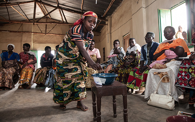 Members deposit savings during a community savings group meeting in Burundi.