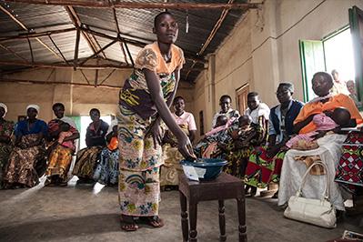 Members deposit savings during a group meeting in Central Burundi.