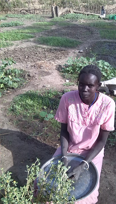 A mother harvests vegetables in South Sudan