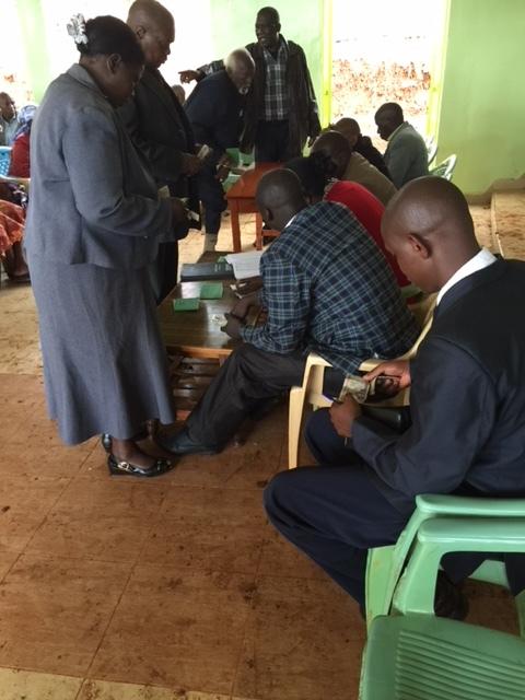 Above: Members deposit savings during a group meeting in Thika, Kenya.