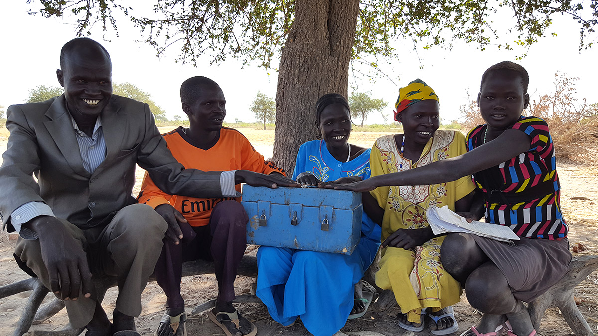 Above: Members of a Savings Group in Warrap State pose with their savings box after recording their weekly contributions. The keys to the three locks are held by different members chosen by their group.