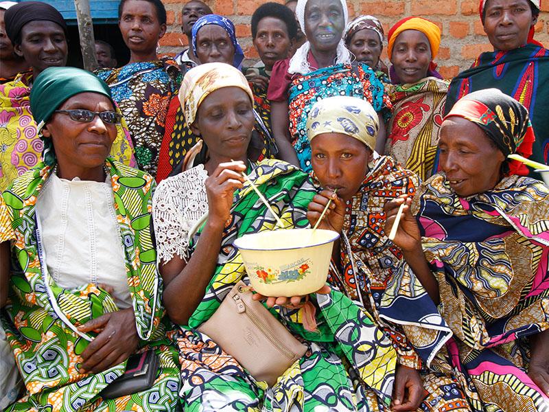 Burundi entrepreneurs share banana juice during a savings group meeting