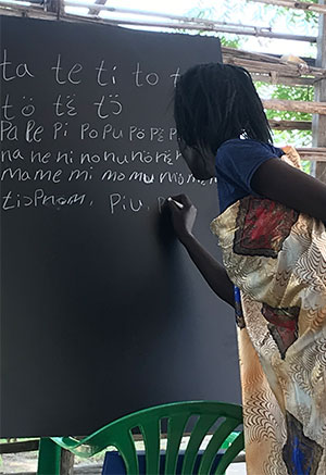 A participant in a Five Talents literacy class practices writing during a lesson in South Sudan.