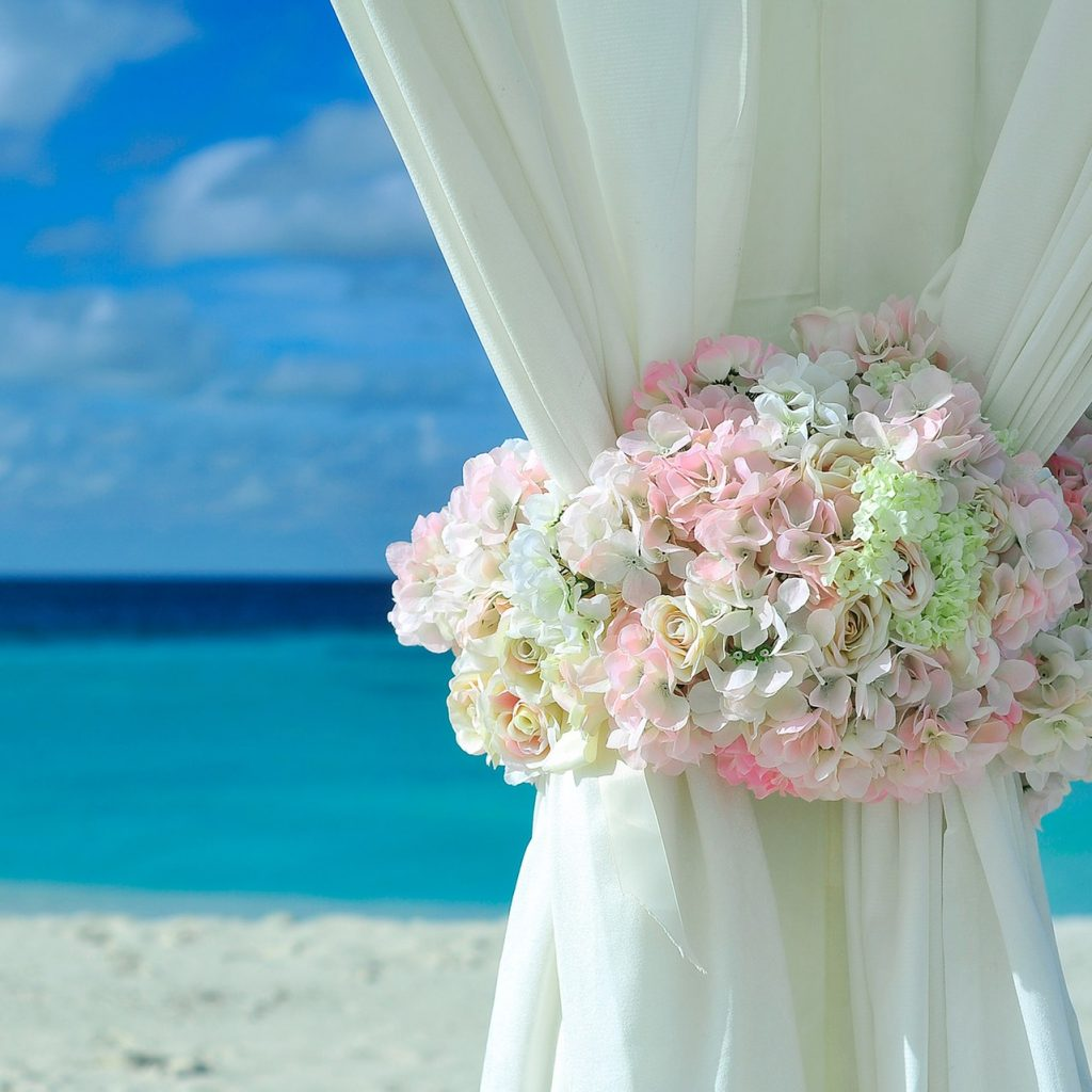 Flowers wrapped around pipe and drape