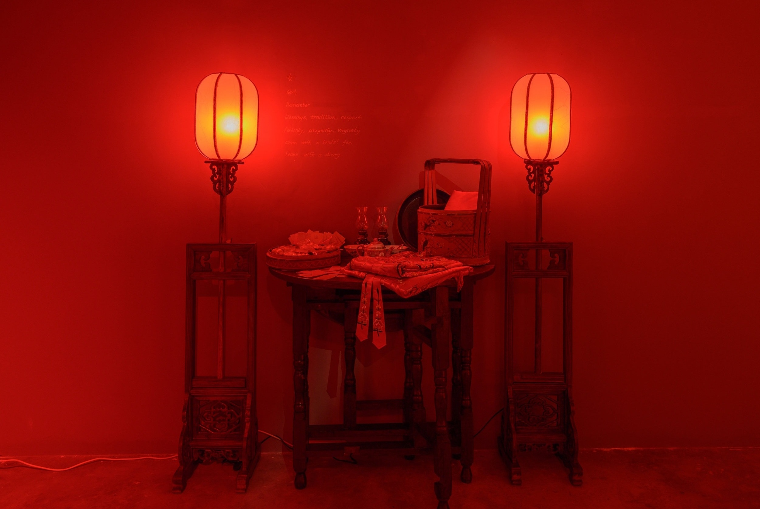 """Girl - Stories of a Woman and Her Dowry""    Two standing lanterns, teak hand-made table, bridal gown, dowry basket, scissors, thread, red fabric, wedding dried fruits, red packets, gold cards, bridal lamps, red bulbs, teapot, tea cups, spoons.  2019 Installation  Solo exhibition at Grey Projects Singapore. Artist Collection.  past series:  Stories of a Woman and Her Dowry"