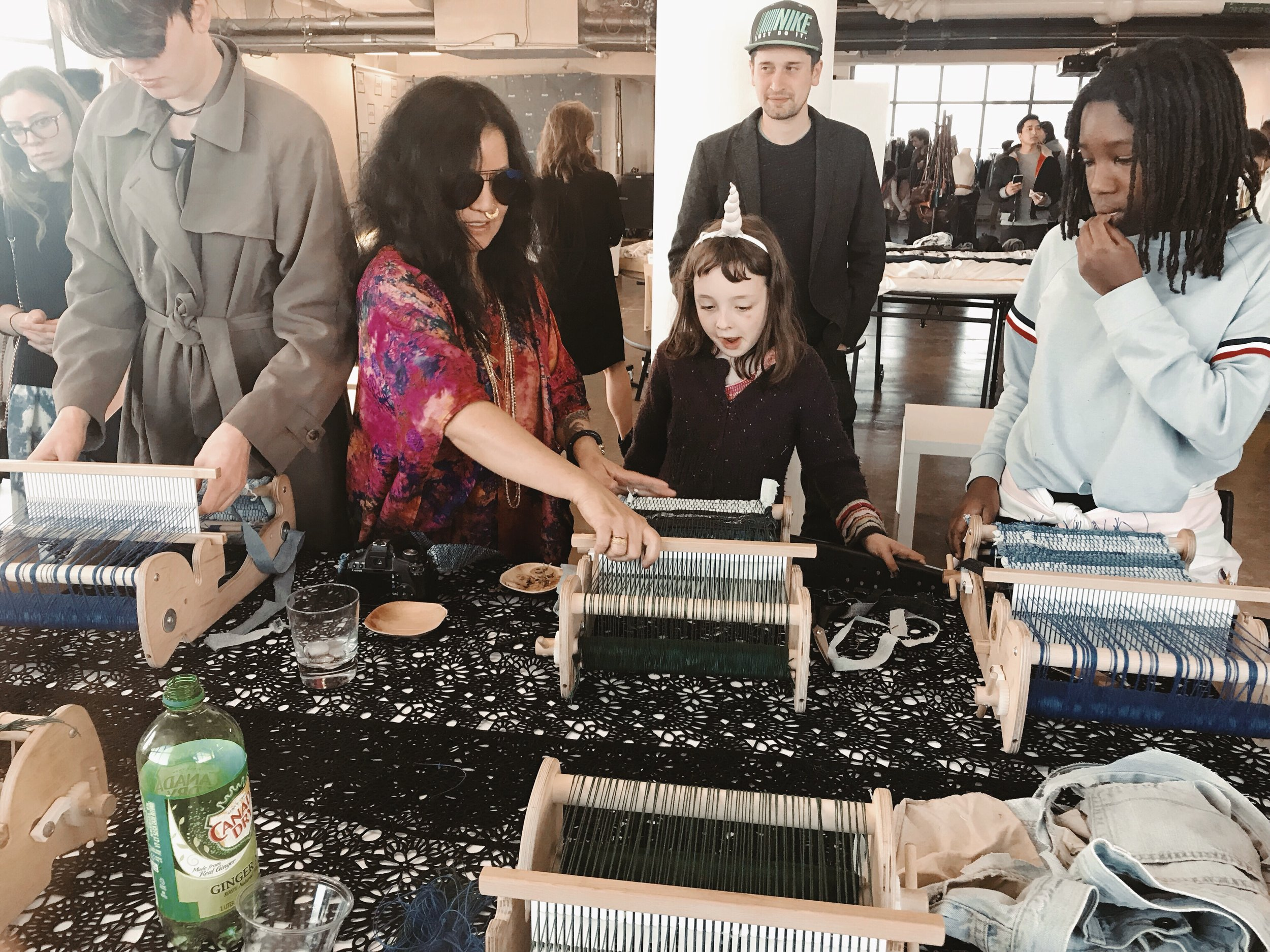 Child learning to weave with old denim at the Brooklyn Fashion and Design Accelerator