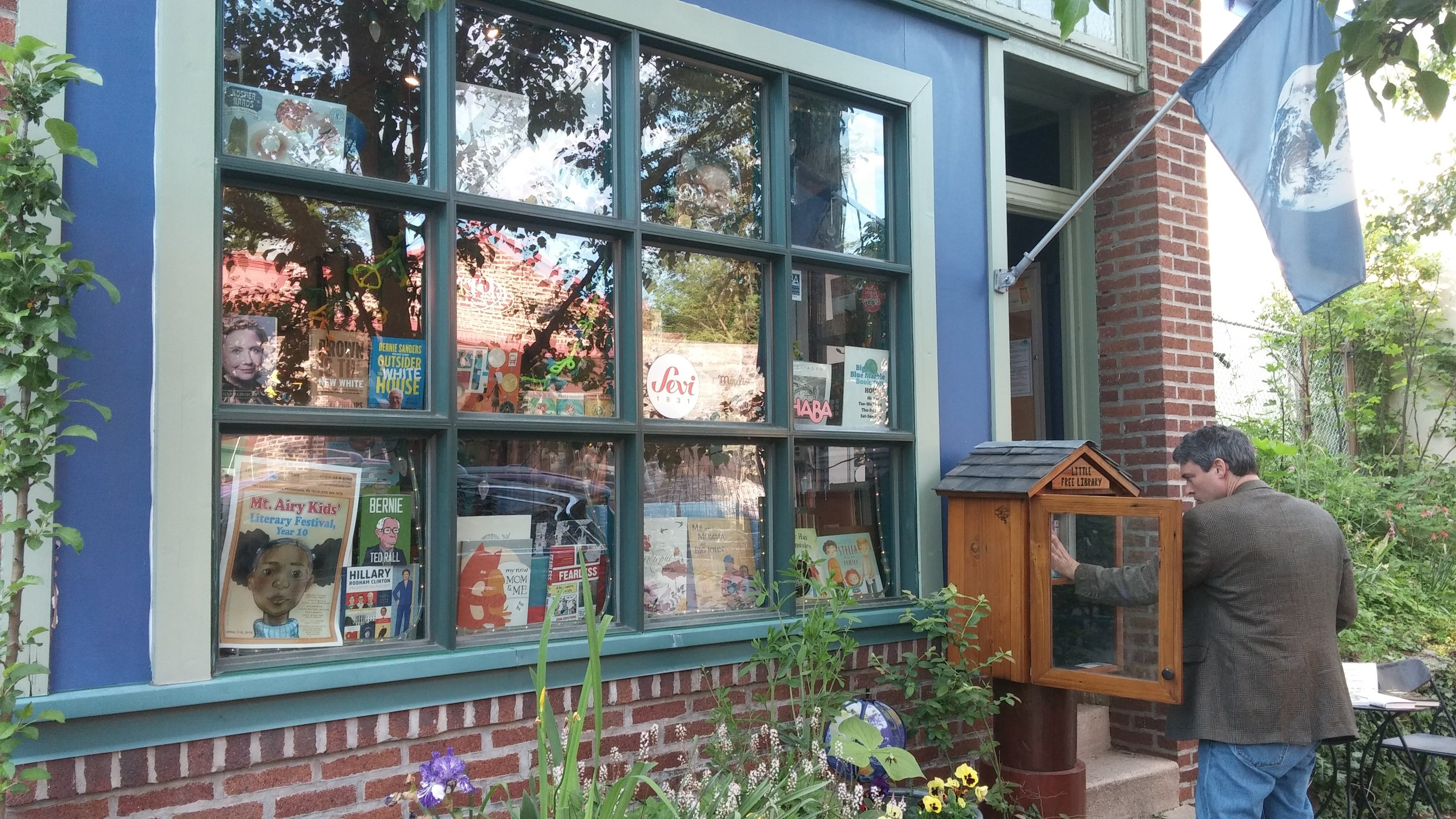 store front with little free library being used.jpg
