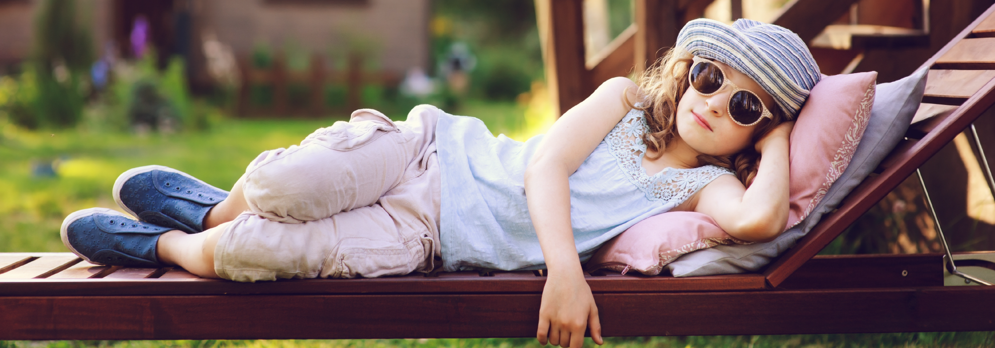 Little girl lounging on chair wearing a hat and sunglasses