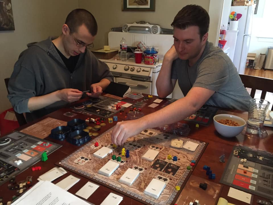 John Brieger (right), at the retreat place working hard placing workers on a worker placement game