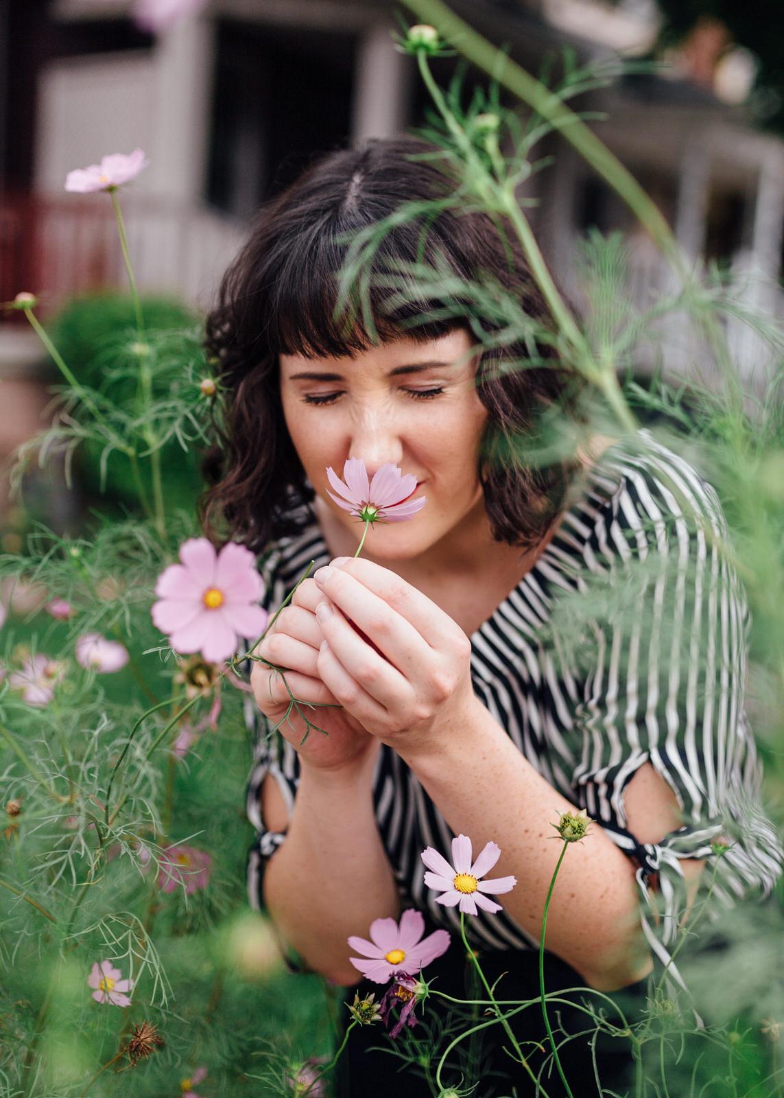 brunette woman smelling flowers