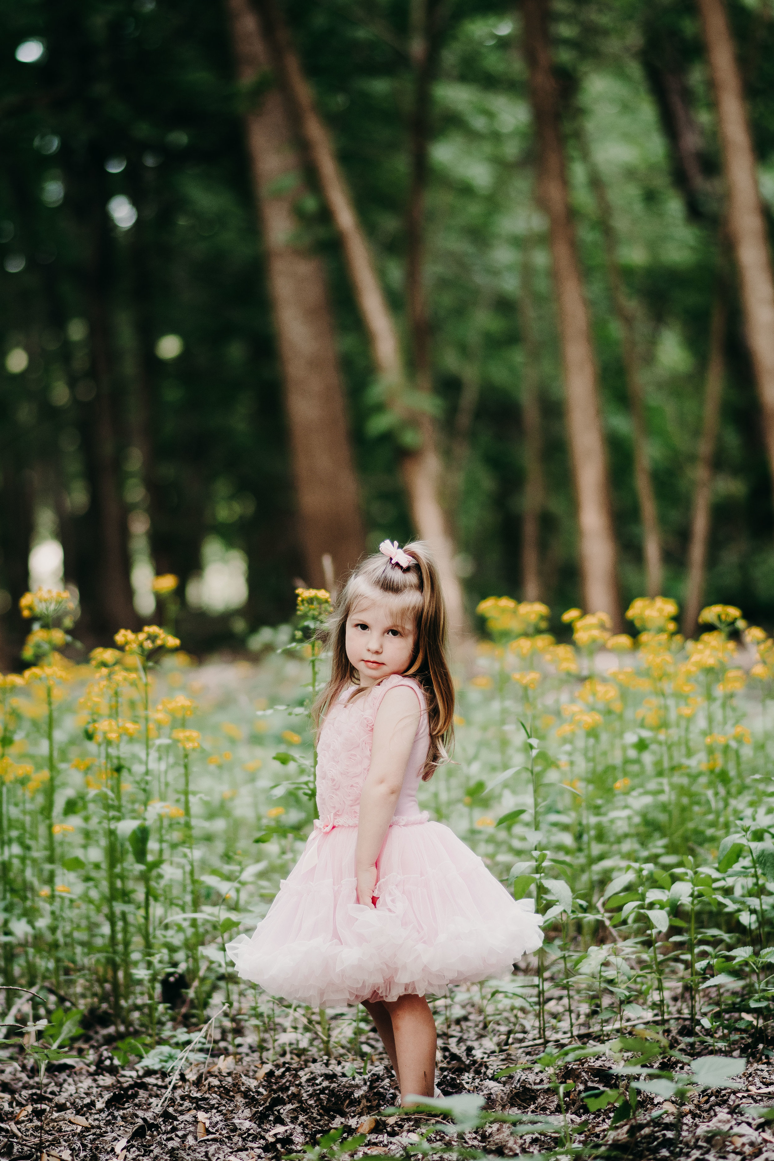I love this shot. Maybe its the wildflowers, maybe its the frilly pink dress in the woods, maybe its the soft light thats diffused by the trees.....or maybe its all of it together! I love it!